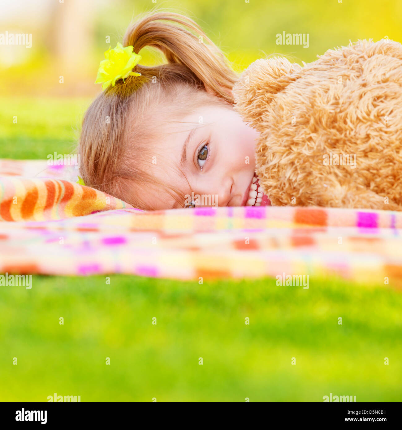 Pretty small girl lying down on green field, playing game with big brown teddy bear, cute child enjoying spring - Stock Image
