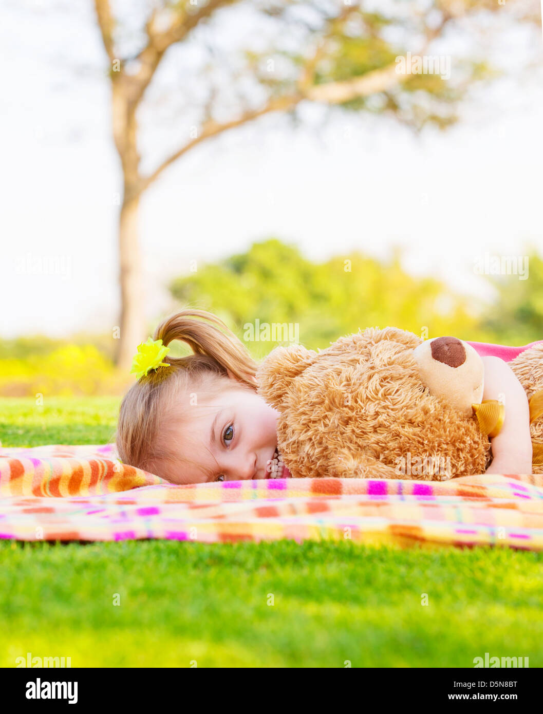 Adorable child resting on backyard in spring time, baby girl laying down on green field with teddy bear, having Stock Photo