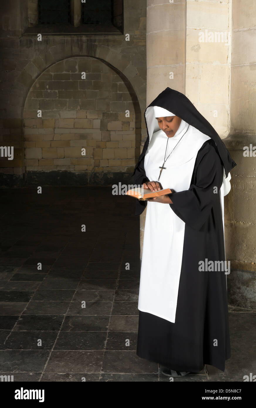 Nun in habit reading the bible in a medieval church - Stock Image