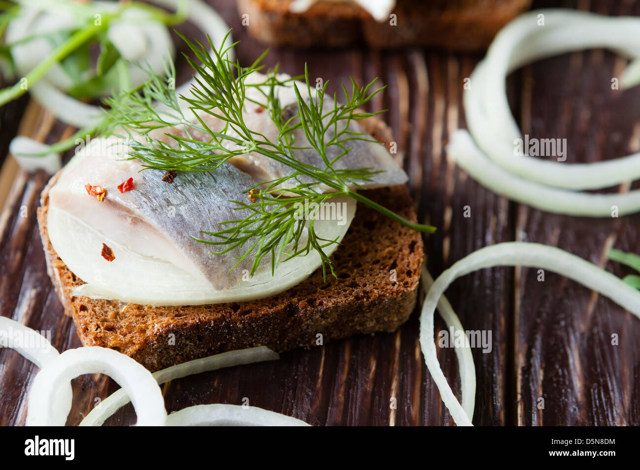 Canapes of black bread and salted herring, closeup - Stock Image