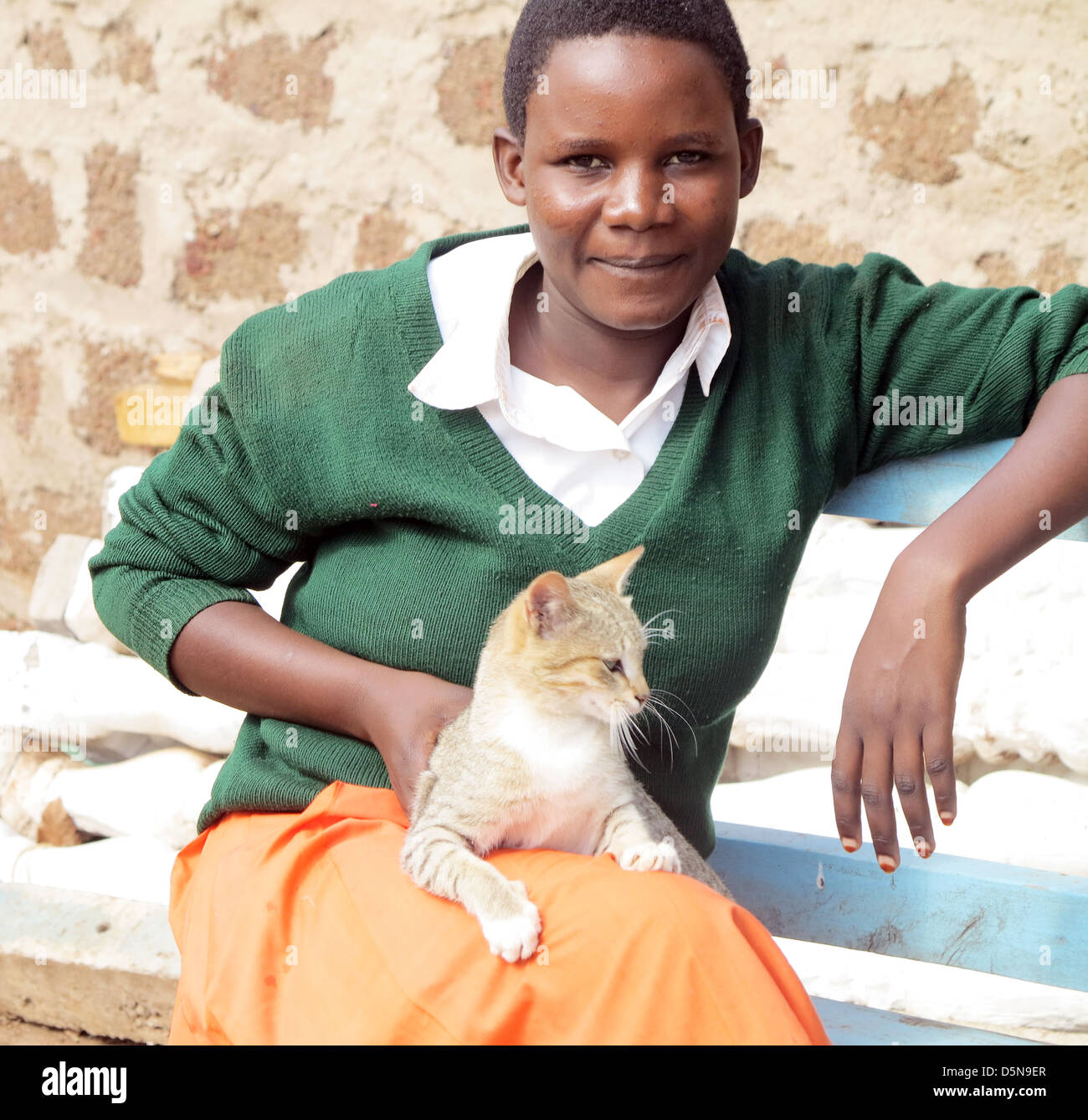 young teenage girls in school uniform and a cat on her knee posing for camera in Moshi;Tanzania;East Africa;Africa - Stock Image