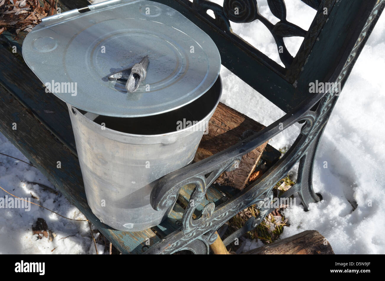 The tools for collecting maple sap - a spigot, cover and bucket, rest on an outdoor country bench. - Stock Image