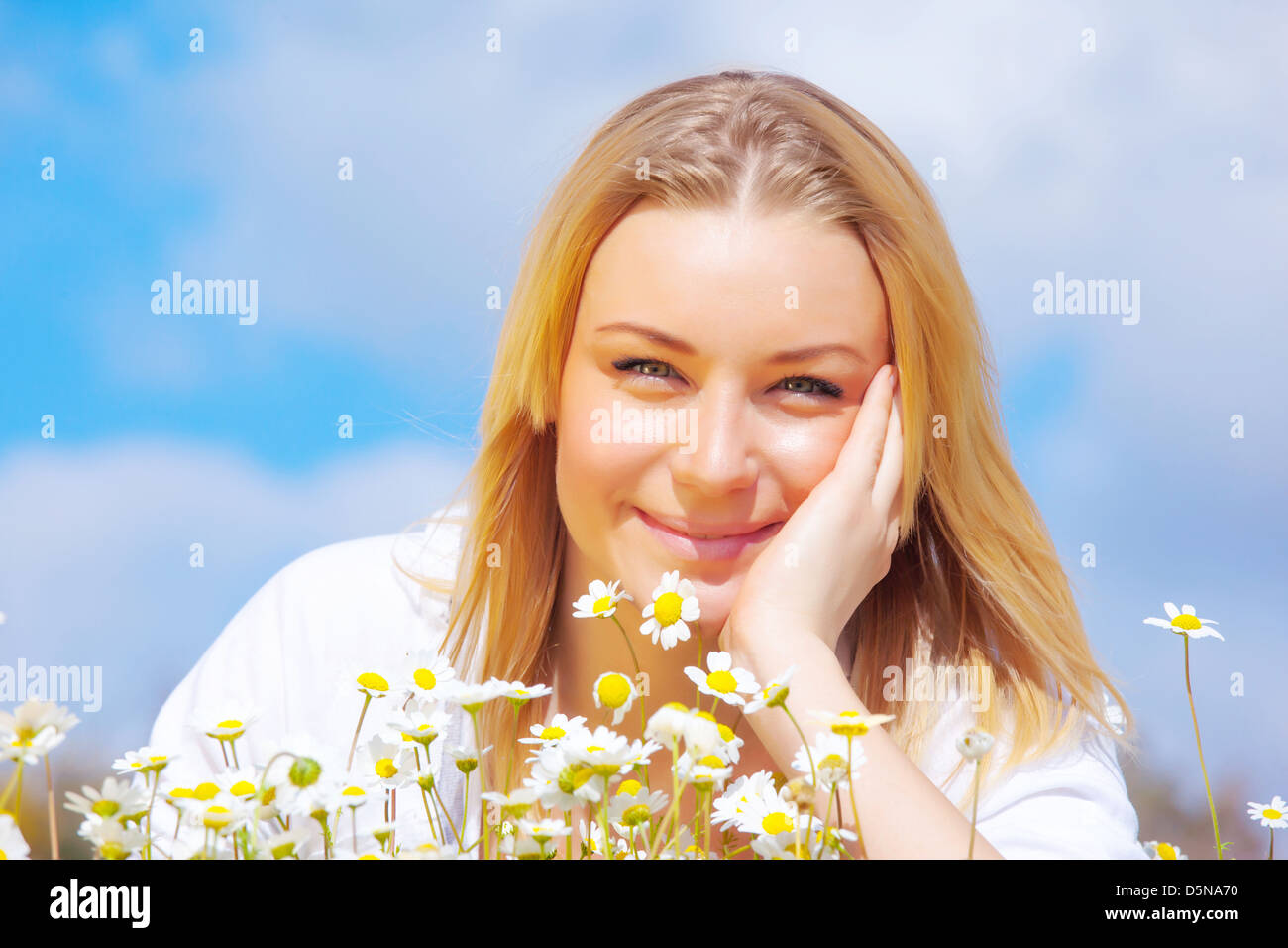Closeup portrait of sweet blond girl on white daisies glade, enjoying summer nature, relaxation and holiday concept - Stock Image