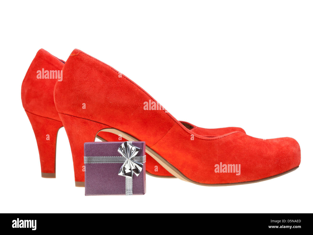 pairs of red high heel pumps with small gift box isolated on white background - Stock Image