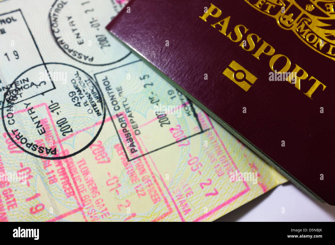 A British passport on top of a heavily stamped visa page. - Stock Image
