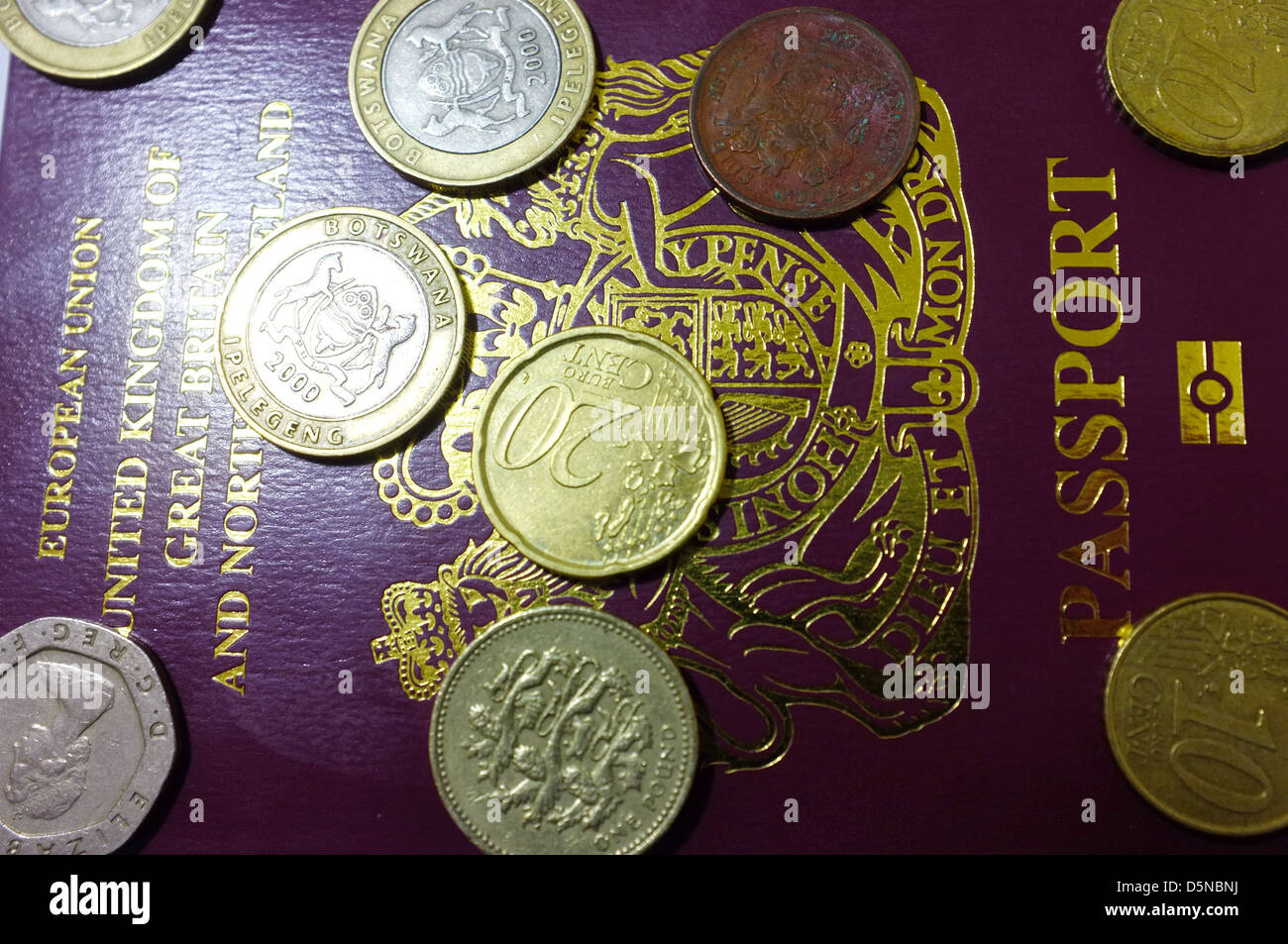 An image of the front page of a British passport covered in coins from the UK and Europe. Stock Photo