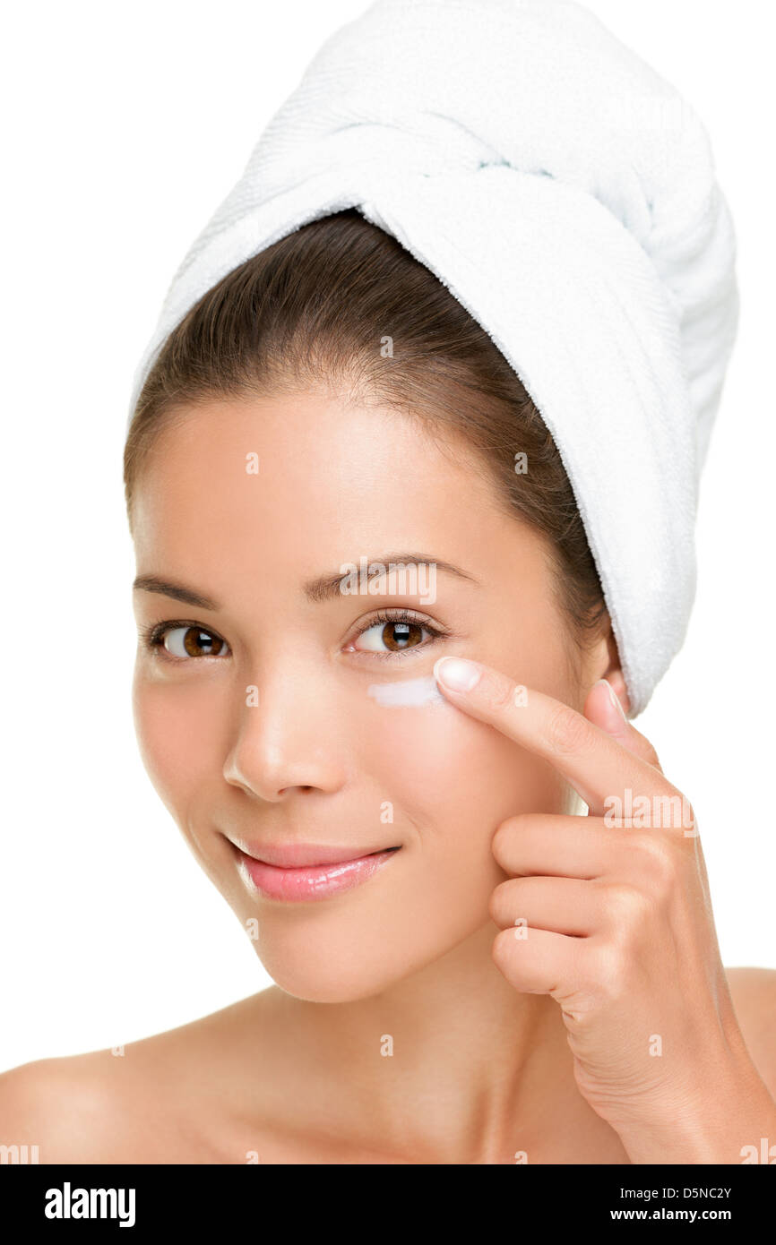 Portrait of beautiful mixed race Asian / Caucasian young woman putting face cream  under eyes isolated on white - Stock Image