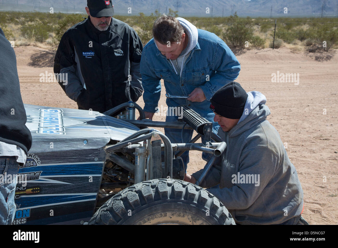 Crew members work on a car in the pits during the Mint 400 off-road auto race through the Mojave Desert - Stock Image