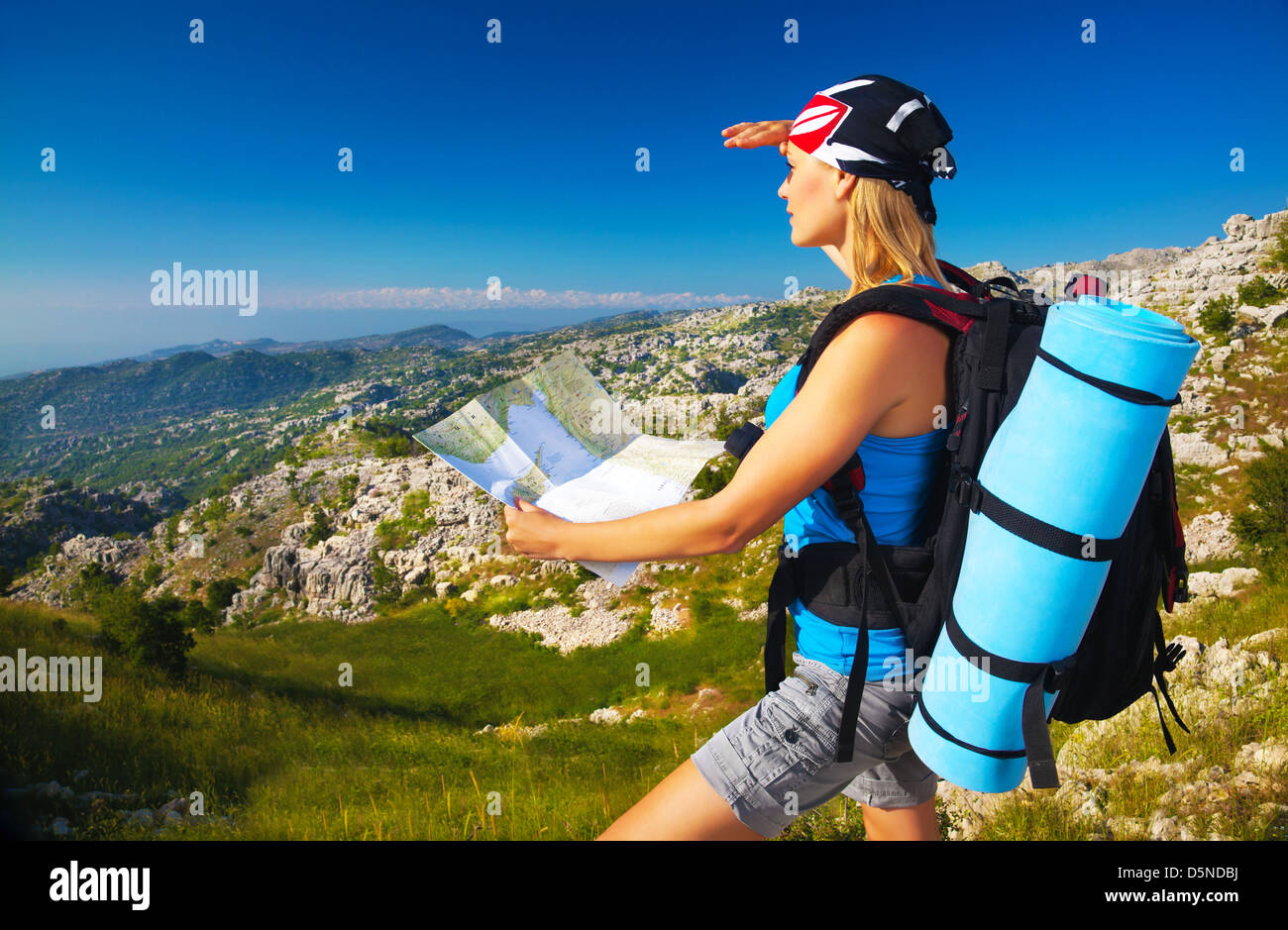 Active young girl searching right track on the map, traveling to high mountains, beautiful landscape, extreme lifestyle - Stock Image