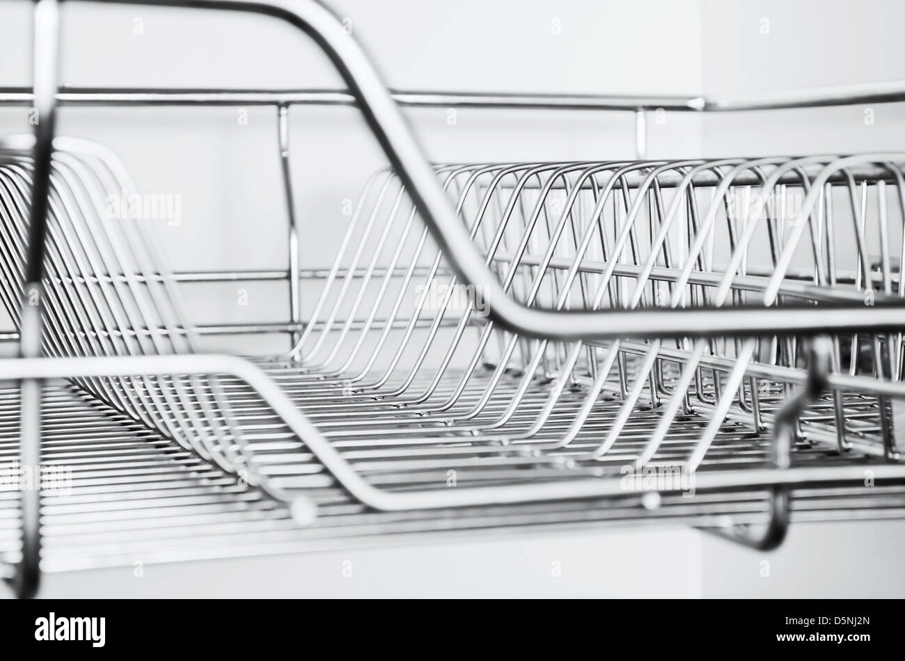 Close Up Of Stainless Steel Dish Rack Inside Kitchen Cabinet