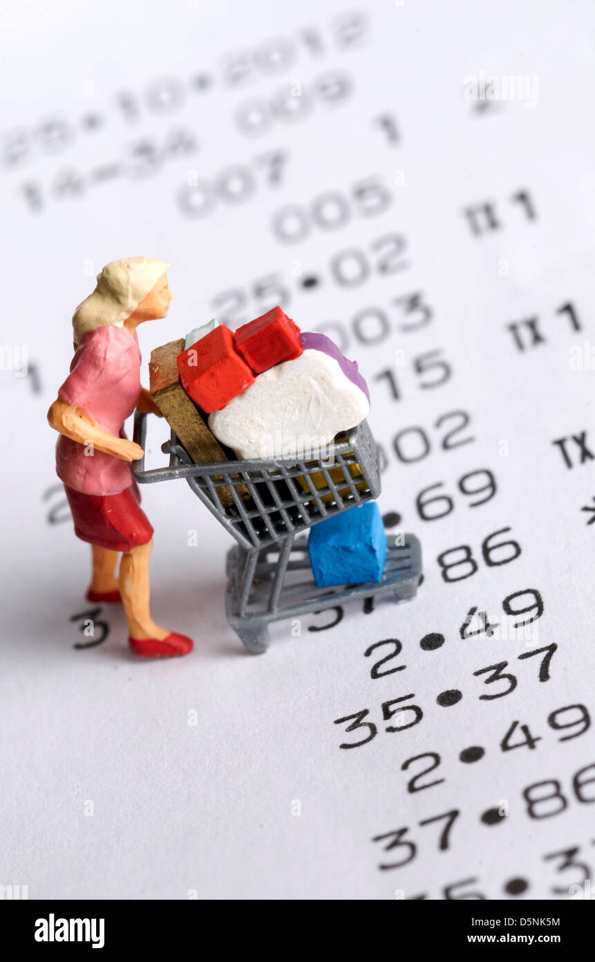 Miniature figurine of a woman with a shopping cart on a receipt - bills / shopping concept - Stock Image