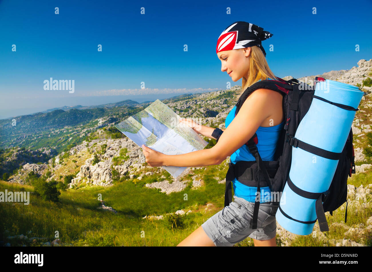 Young sporty woman standing on the peak on mountain watching on map, extreme adventure, happiness and freedom concept - Stock Image