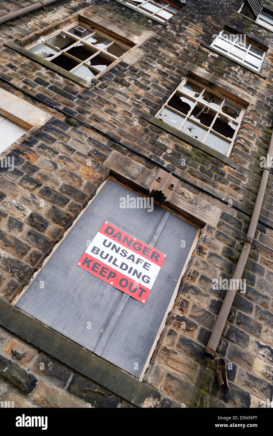 Danger unsafe building keep out sign on a disused mill building in Lancashire, England. - Stock Image
