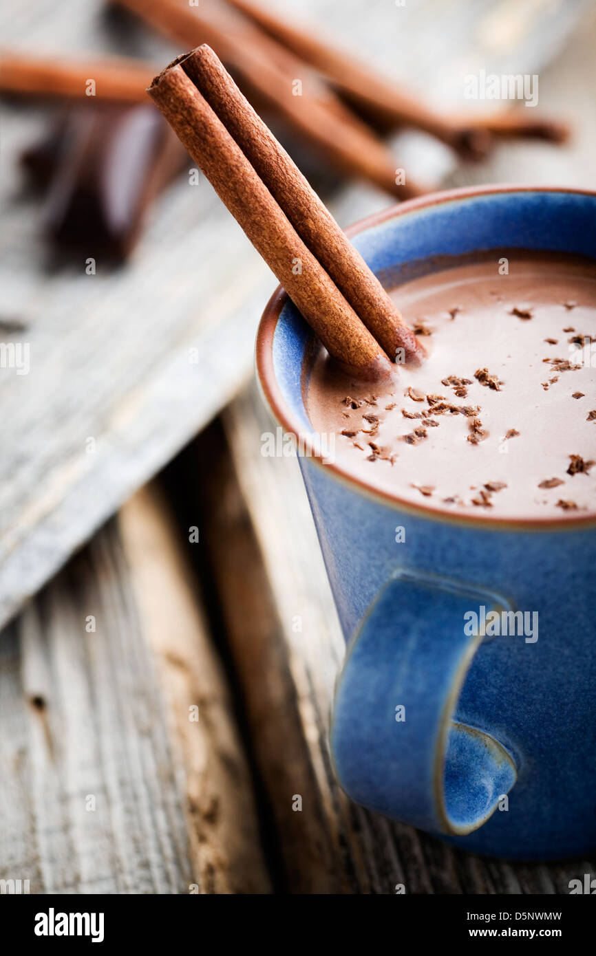 Hot chocolate with cinnamon stick in blue cup - Stock Image
