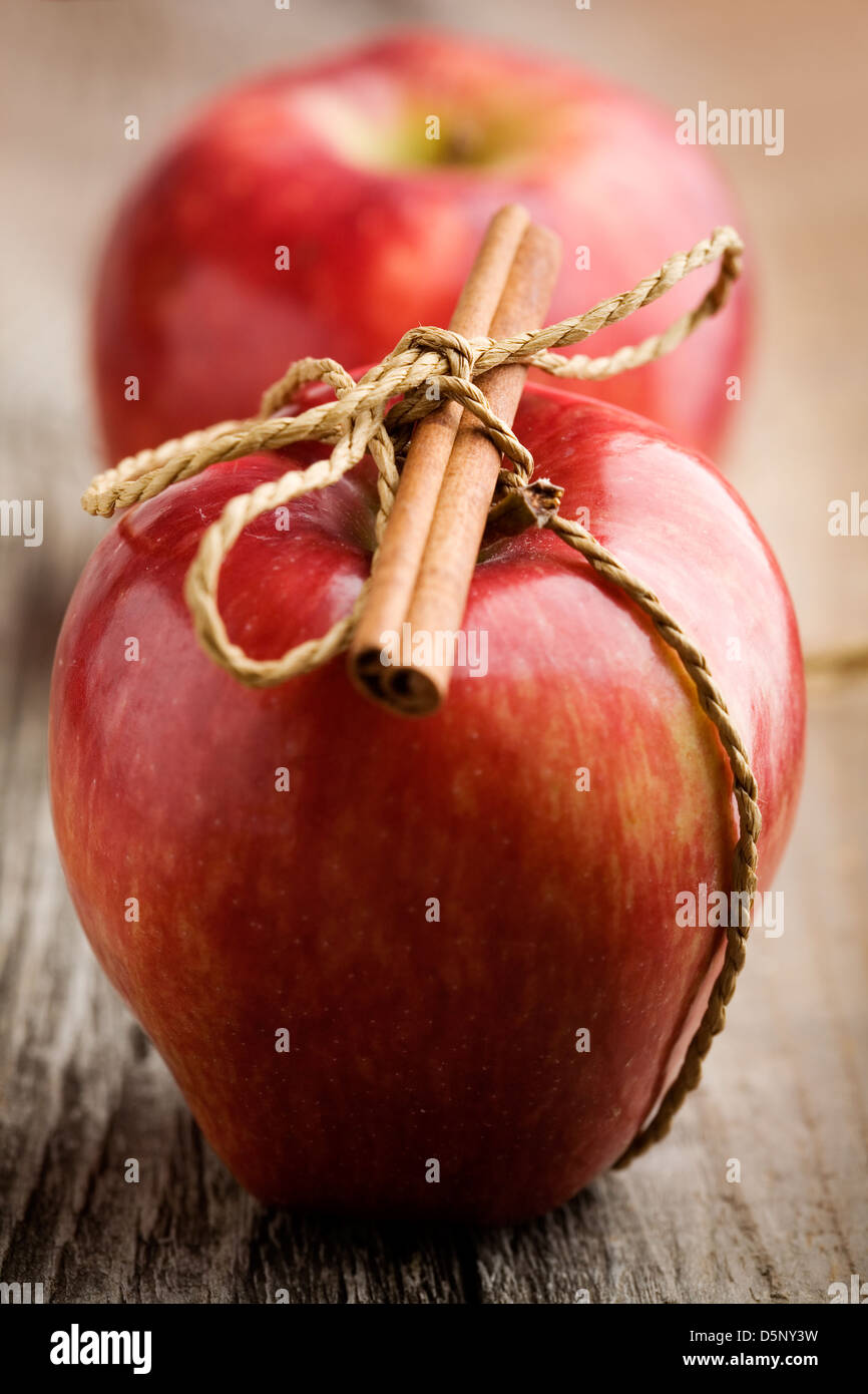 Red apples with cinnamon stick, shallow focus - Stock Image
