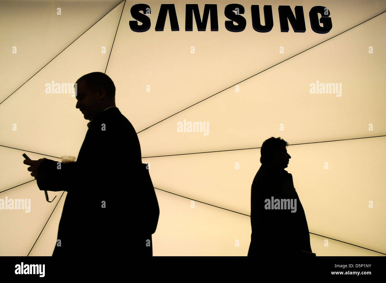 shadows silhouette of customers walking next to the Samsung stand at World Mobile Congress in Barcelona 2013. 270213. - Stock Image