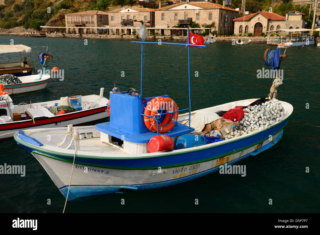 Fishing boats and hotels in the picturesque hamlet of Assos Iskele or Behram Turkey on the Aegean Sea - Stock Image