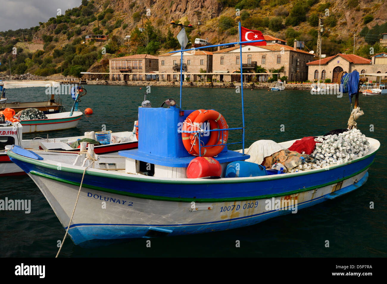 Fishing boats and hotels in the picturesque hamlet of Assos Iskele Turkey on the Aegean Sea - Stock Image