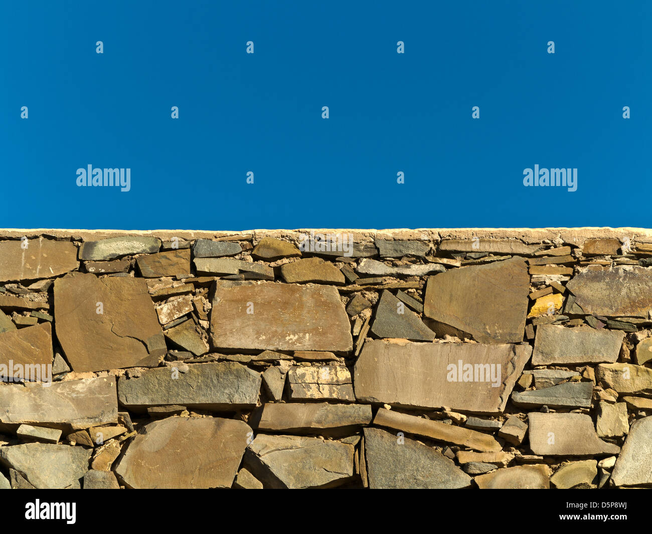 Close up of stone wall construction with blue sky - Stock Image