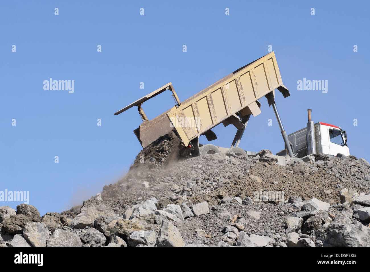Dump truck lorry dumping soil and stones on construction area - Stock Image
