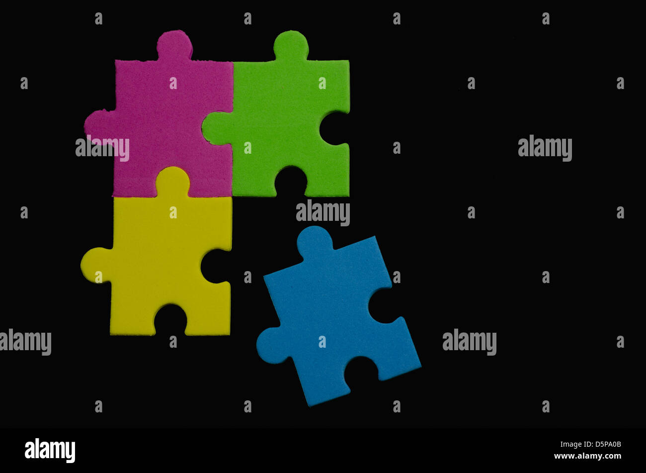 Colorful puzzle pieces over black background representing variety and tolerance - Stock Image