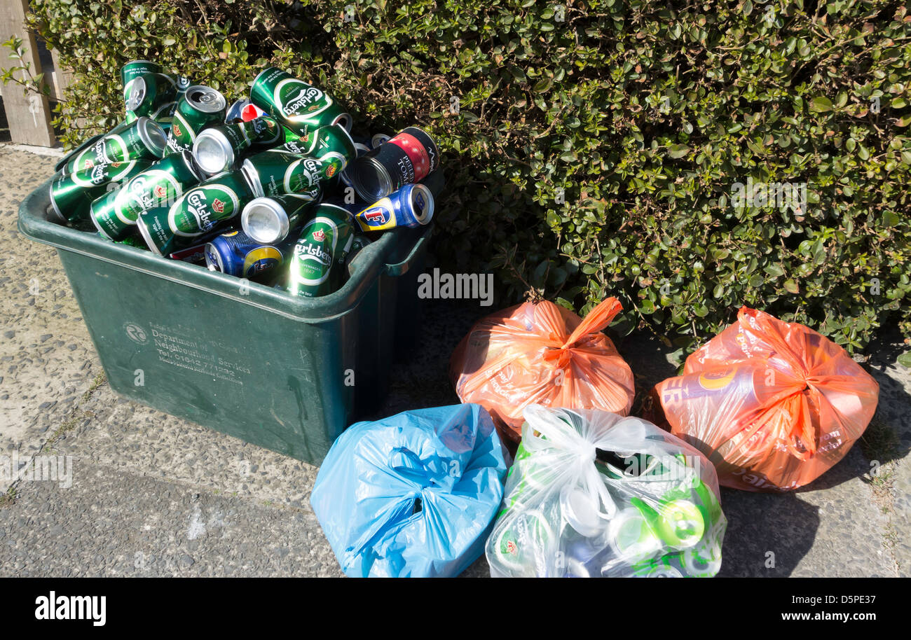 Recycling Green box for bottles and tins filled with Lager cans. The box is too small and plastic bags are filled - Stock Image