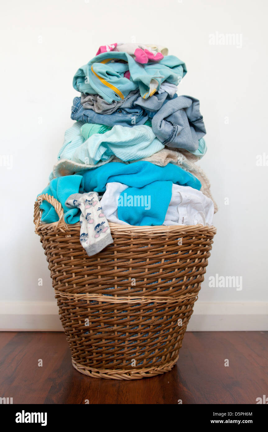 Wicker laundry basket over-filled with washing - Stock Image