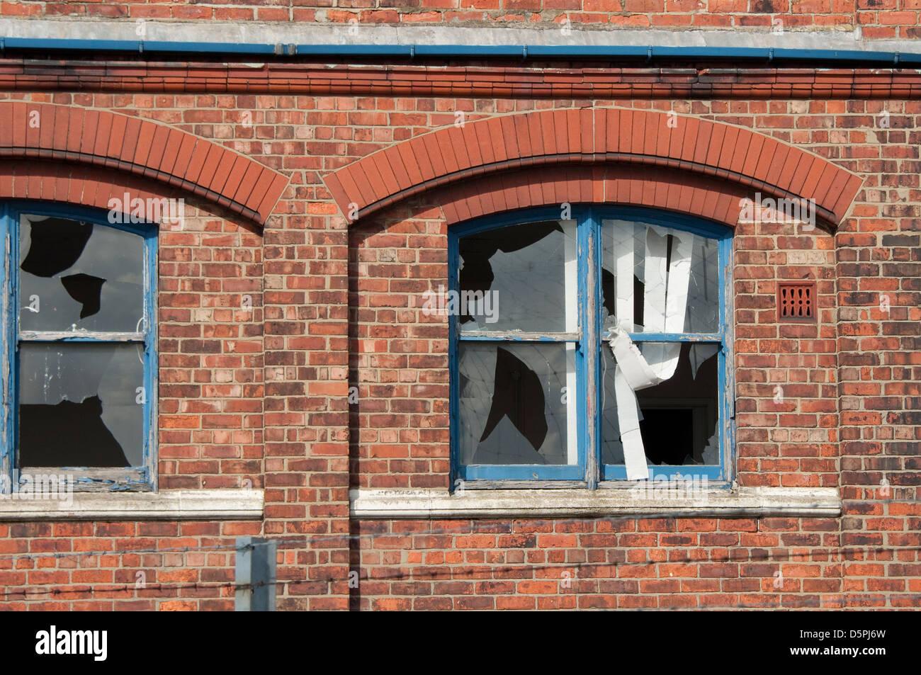 Broken windows on derelict building - Stock Image