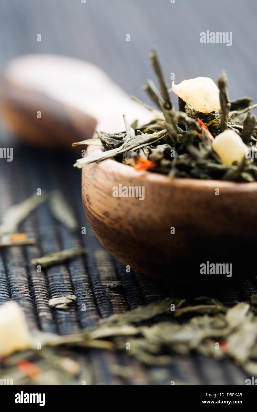 Fresh green tea leaves on wooden spun - Stock Image