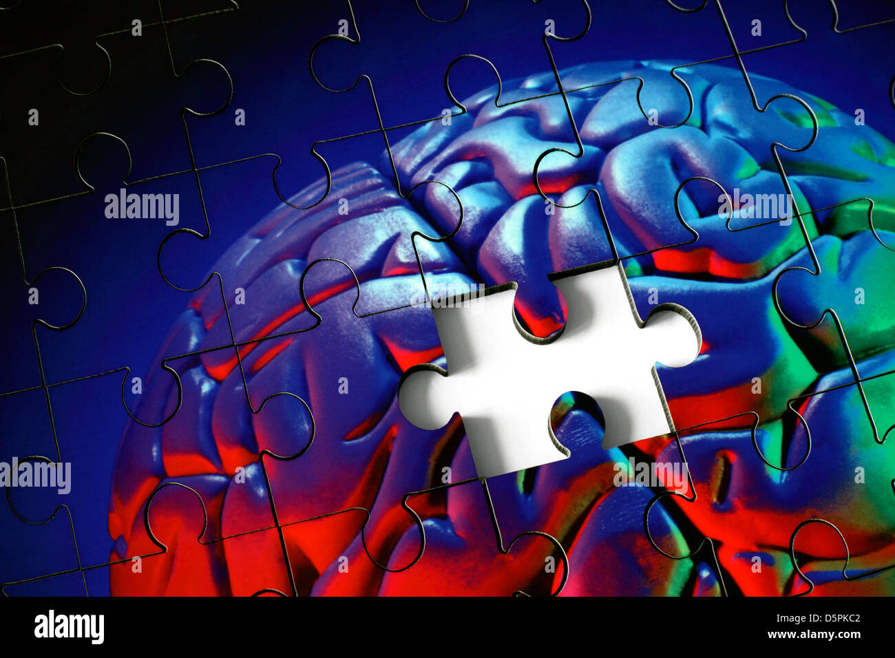 A piece missing from a jigsaw puzzle made from a photograph (with coloured flash) of a plastic model human brain. - Stock Image