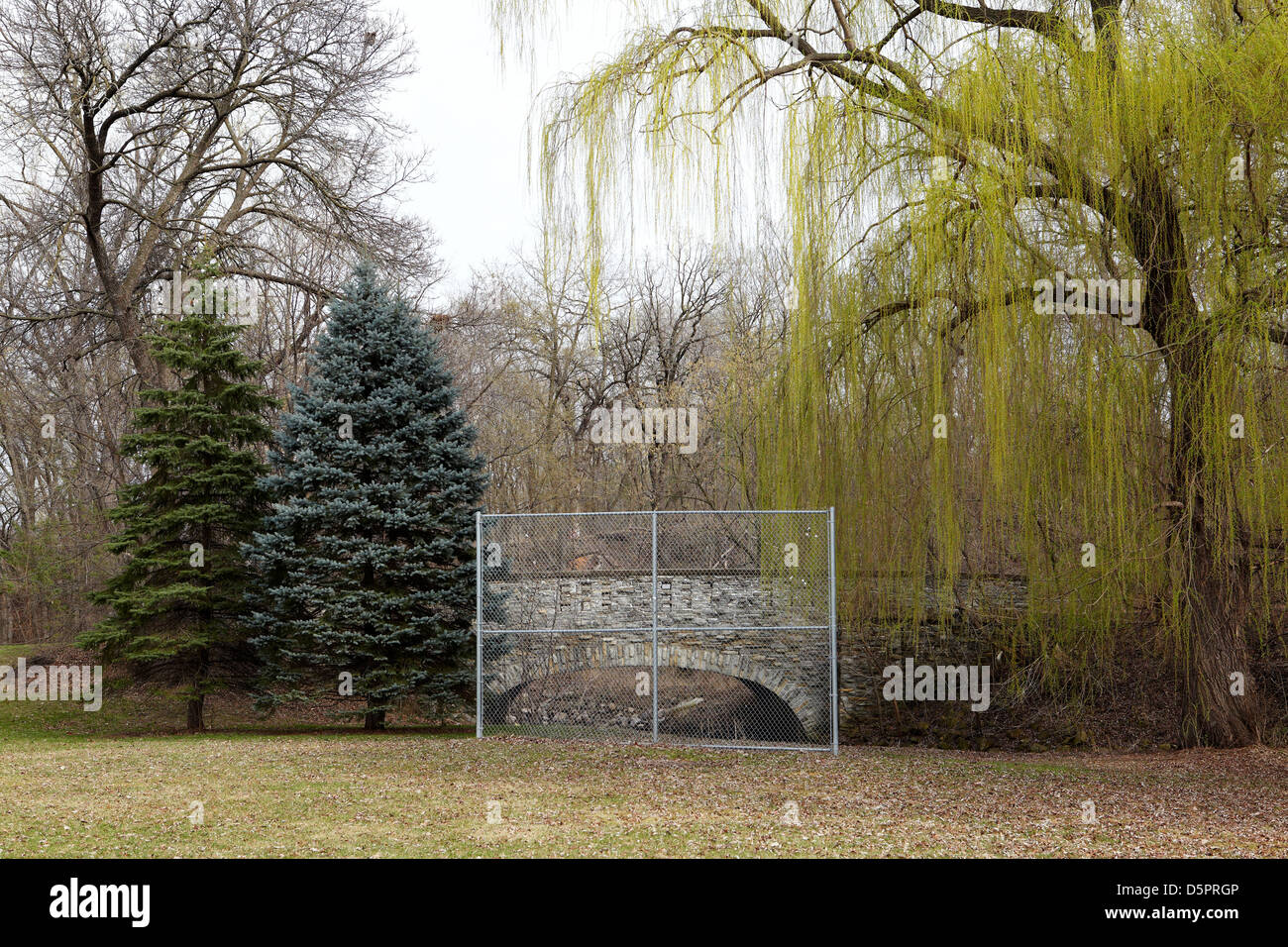 Chain link fence framing a bucolic Spring landscape - Stock Image