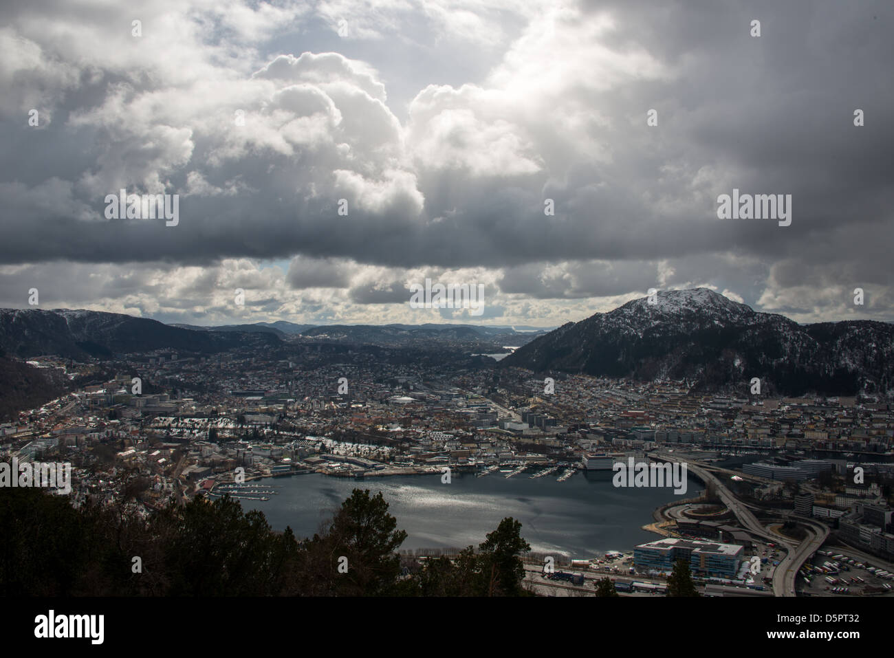 April sun over Bergen City centre south part during undtable weather as a snow cloud emerges from the North Sea. - Stock Image