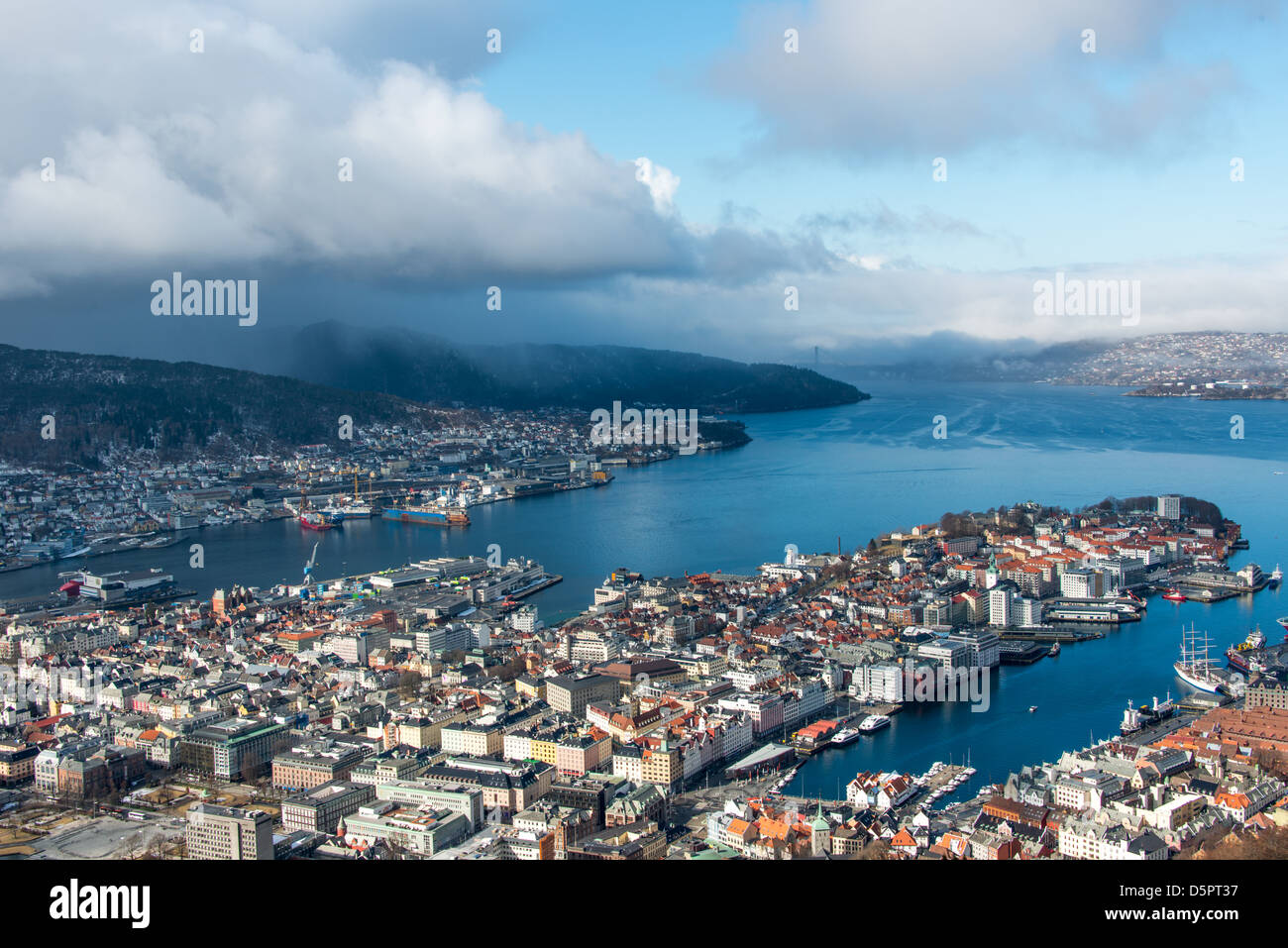 April sun over Bergen City centre as a snow cloud emerges from the North Sea. - Stock Image