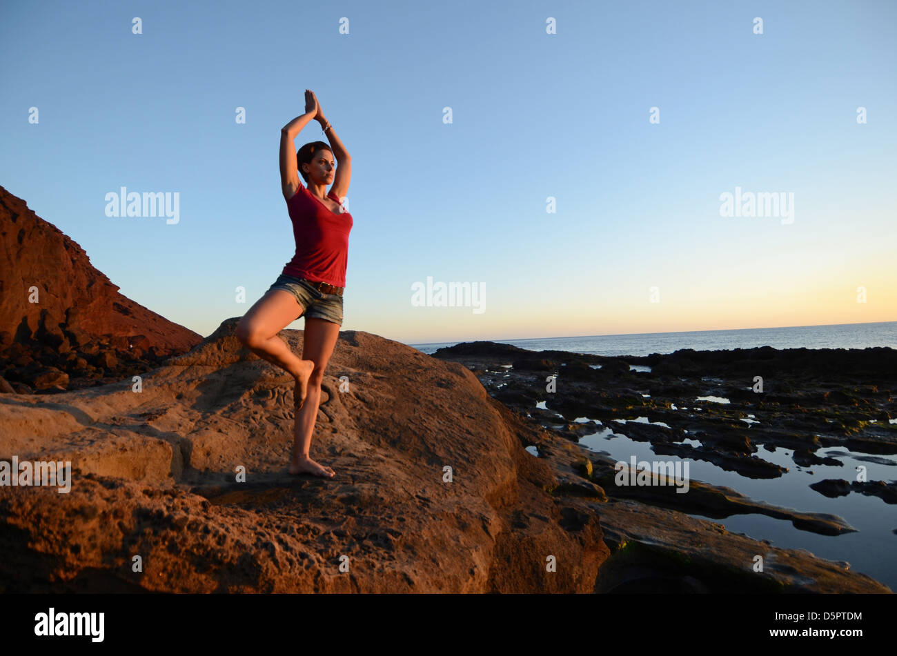 Young woman in tree pose, on the coast - Stock Image