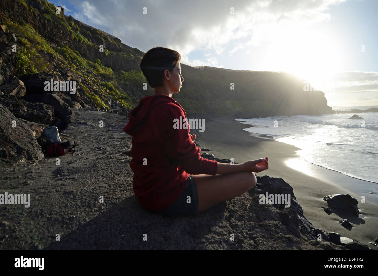 Young attractive woman meditates in lotus pose, in front of the coast. - Stock Image