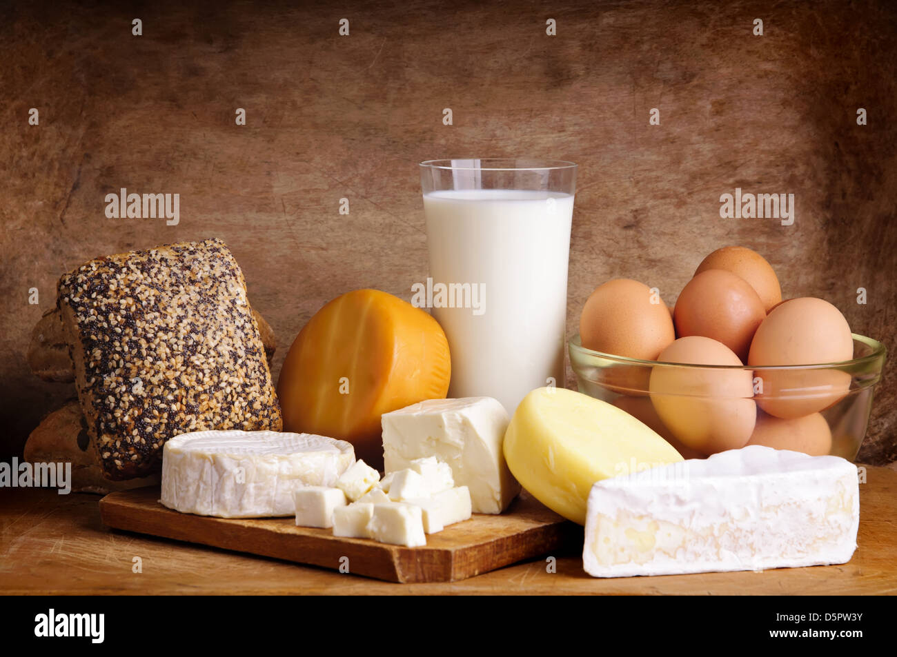 still life with dairy products, milk, eggs, bread and chees on a vintage wooden background - Stock Image