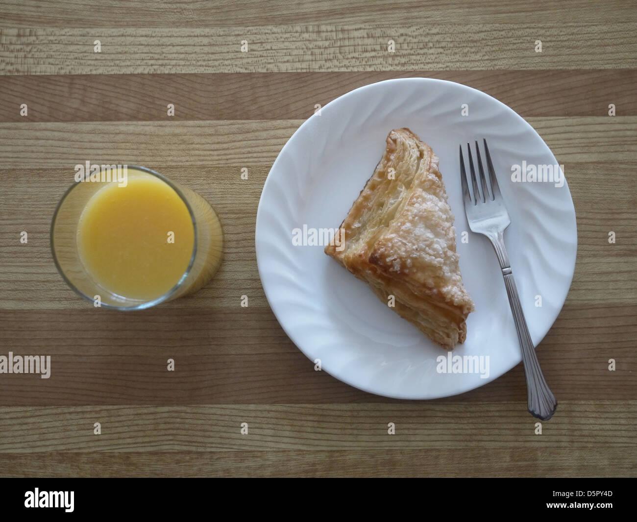 orange juice apple turnover plate fork - Stock Image