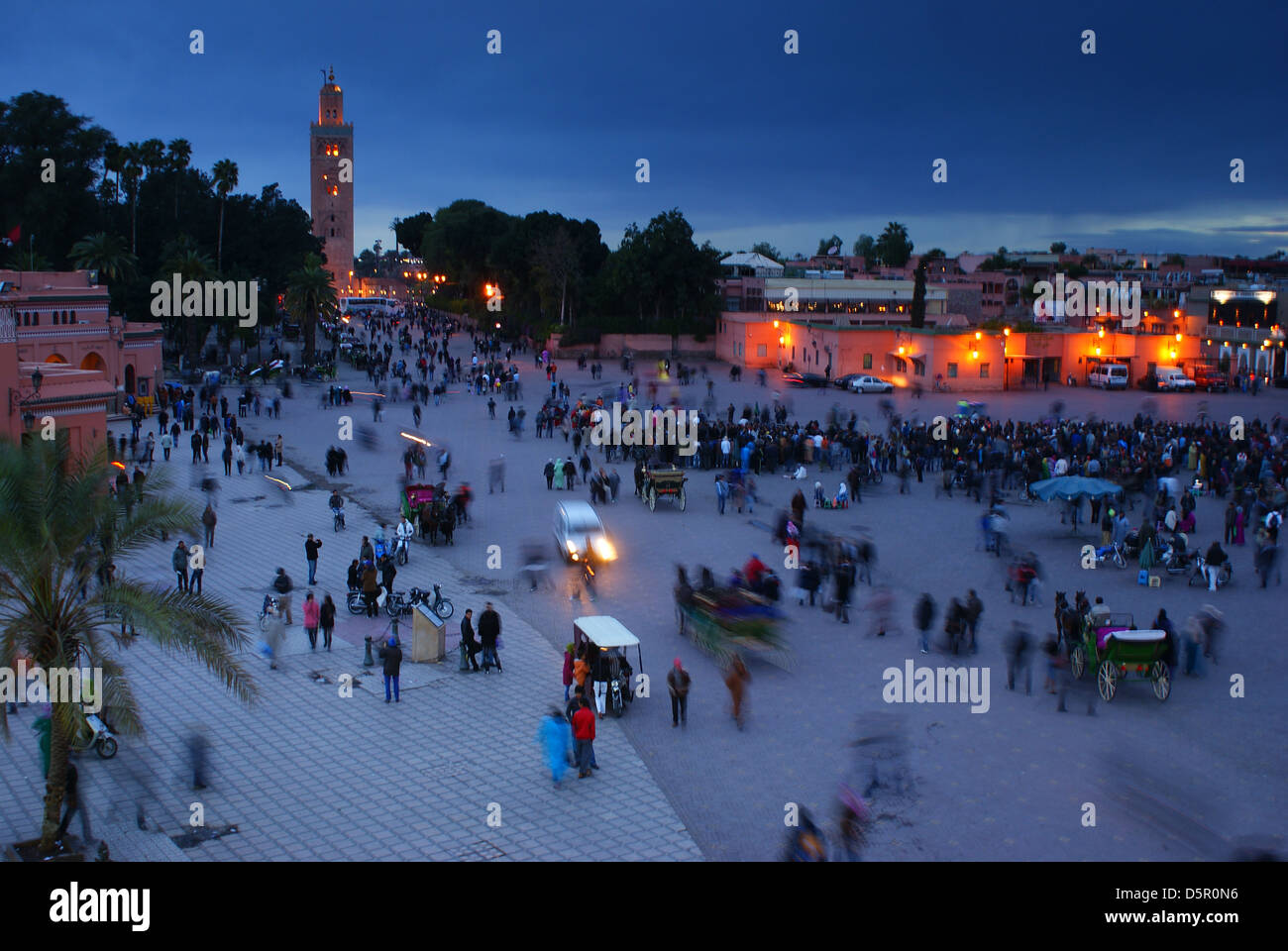 Djemaa el Fna, the main square in Marrakech, Morocco, at dusk, with the minaret of the Koutoubia Mosque in the background. Stock Photo