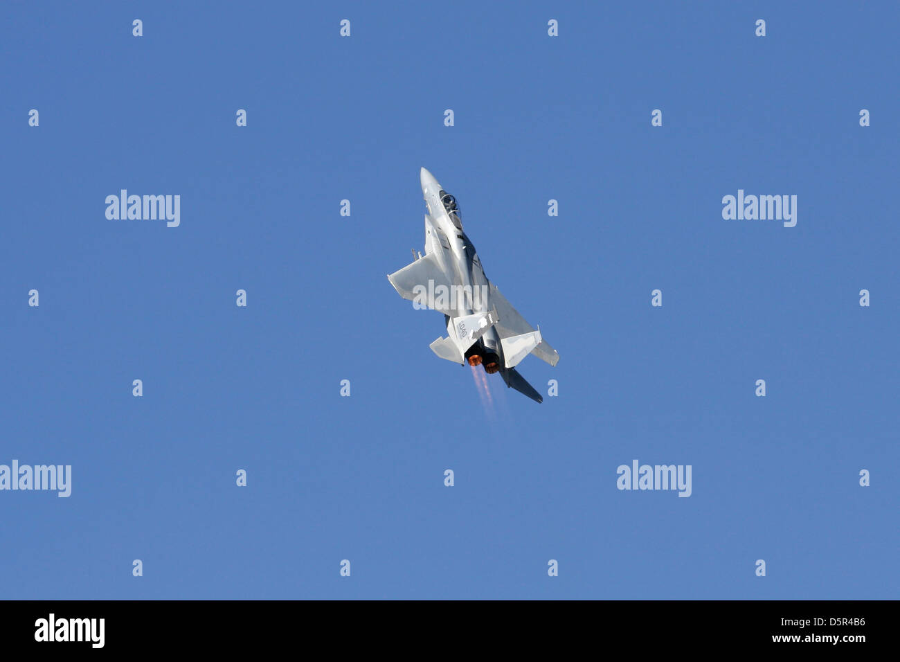 F-15 Military Jet in a climb with afterburners shooting flames. Stock Photo