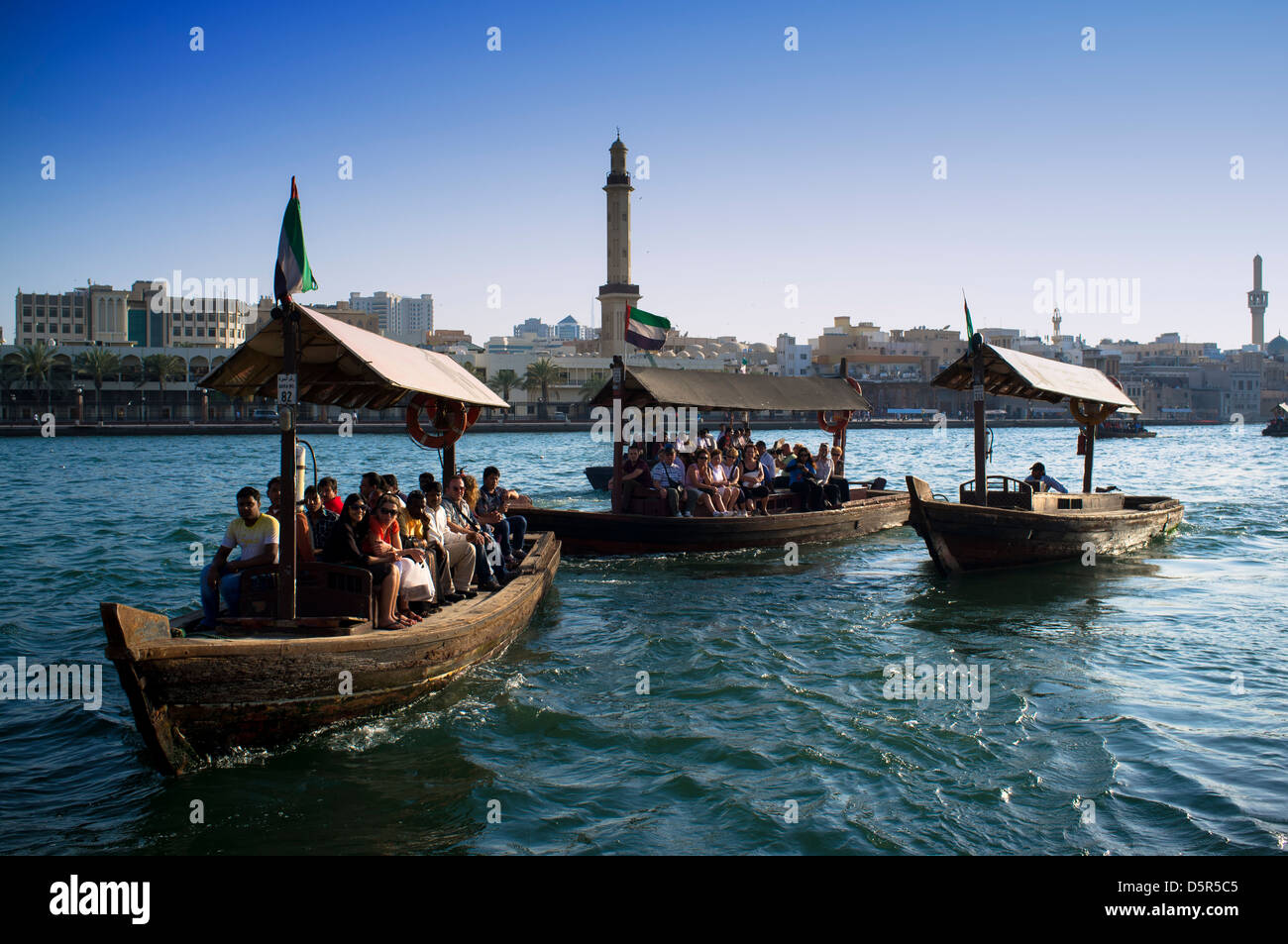 Traditional Abra water ferries crossing The Creek at Deira in Dubai United Arab Emirates - Stock Image