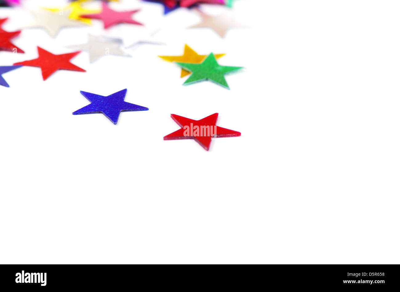 Christmas decoration of colored confetti stars against white background Stock Photo