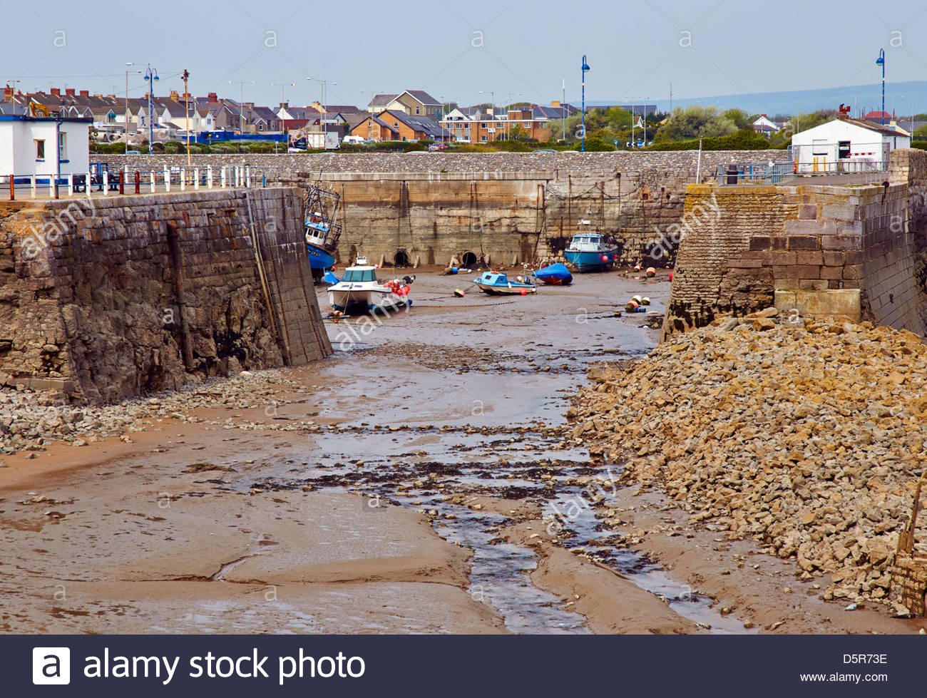 the harbour in porthcawl with the tide out and moored motor boats - Stock Image