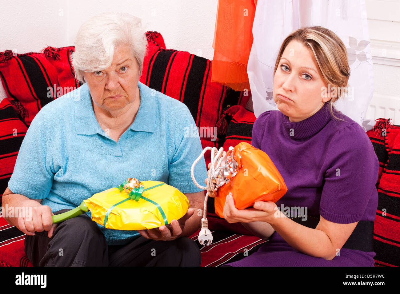 old and young woman are getting uninspired gifts - Stock Image