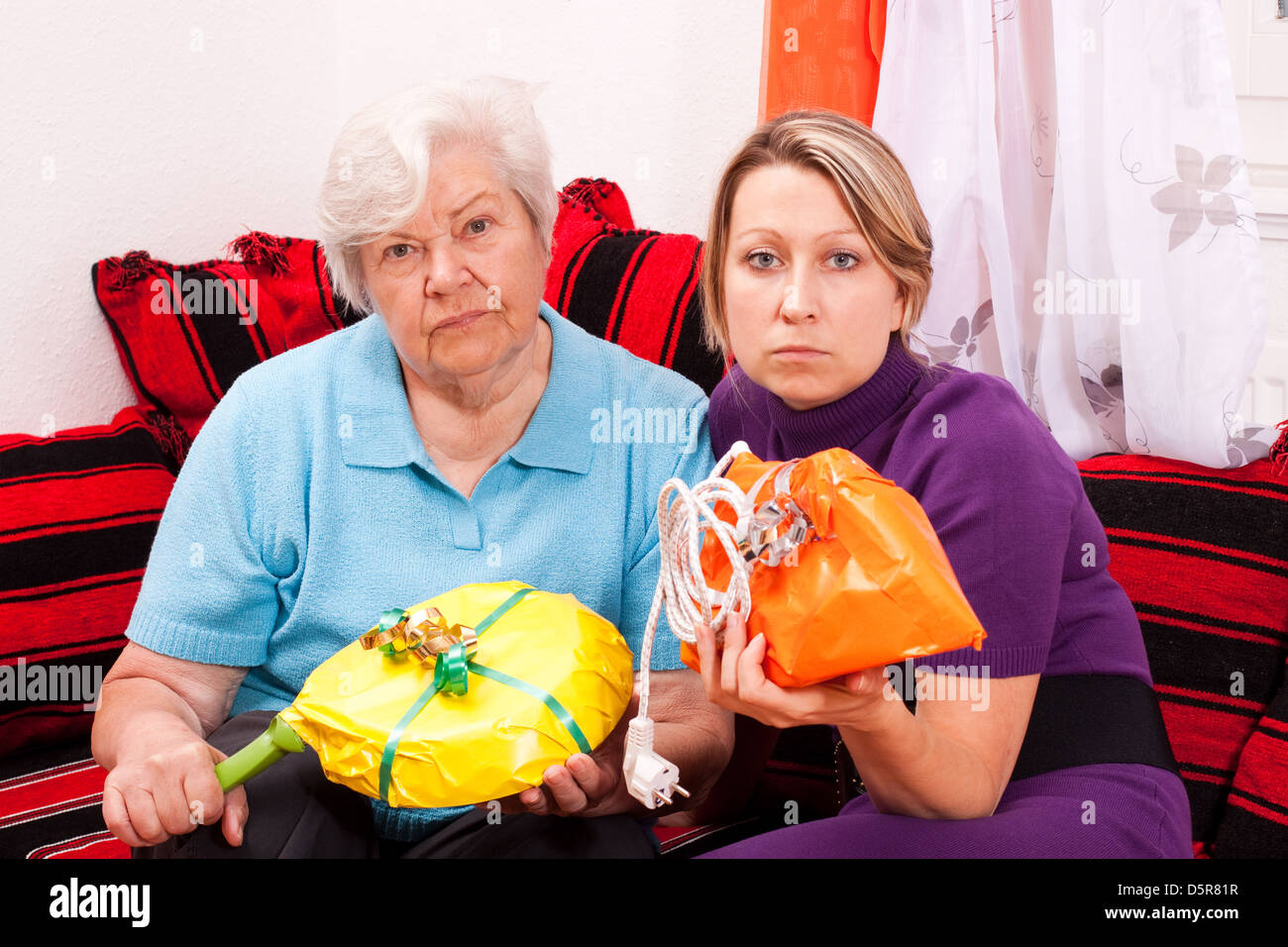 old and young woman are getting improper gifts - Stock Image