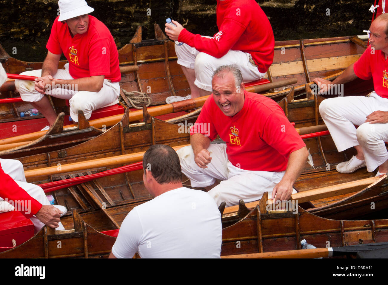 Members of The Queen's Swan Uppers share a joke while performing the annual swan upping ceremony along the river - Stock Image