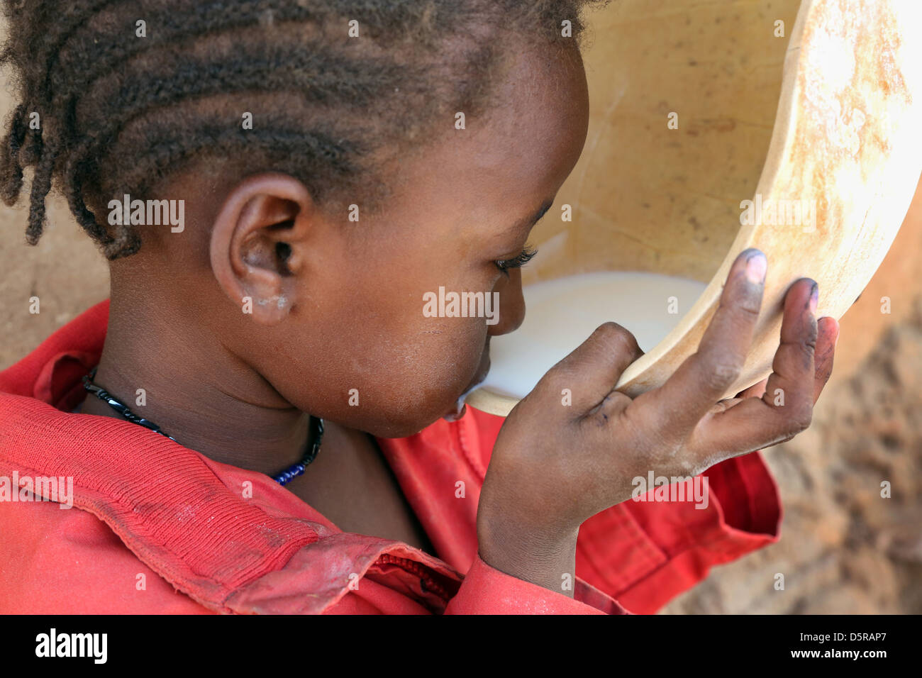 Girl drinks cow's milk from a calabash, Burkina Faso - Stock Image