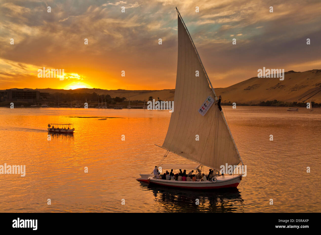 Traditional wooden sailing boats or Feluccas at sunset sailing on the river Nile at Aswan Egypt Middle East Stock Photo