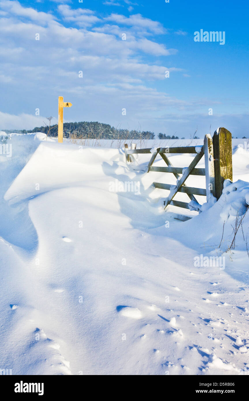 Drifting snow covering a gate, public footpath sign, walls and fields Derbyshire peak district England, GB, UK, - Stock Image