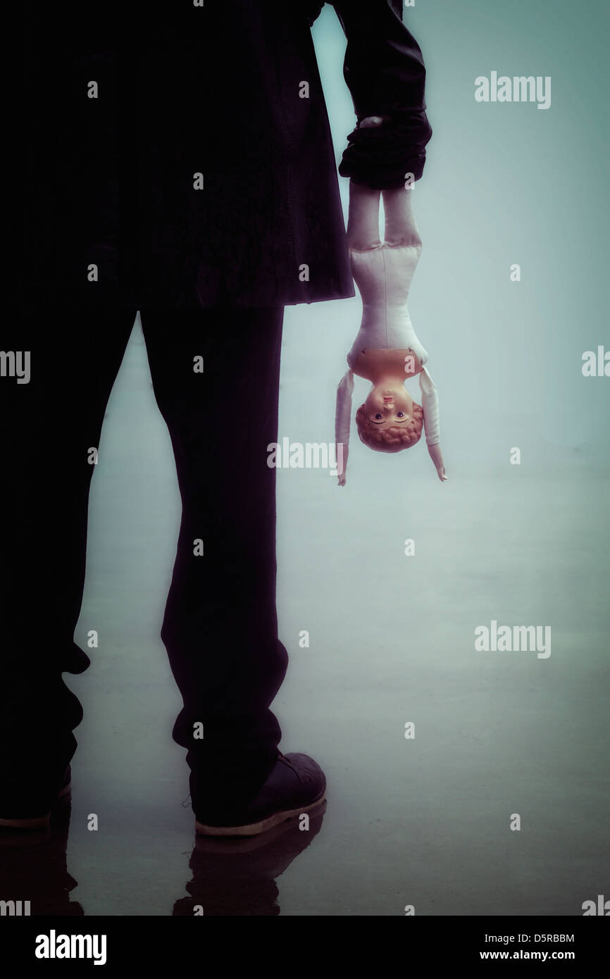 a dark man with an old, vintage doll - Stock Image