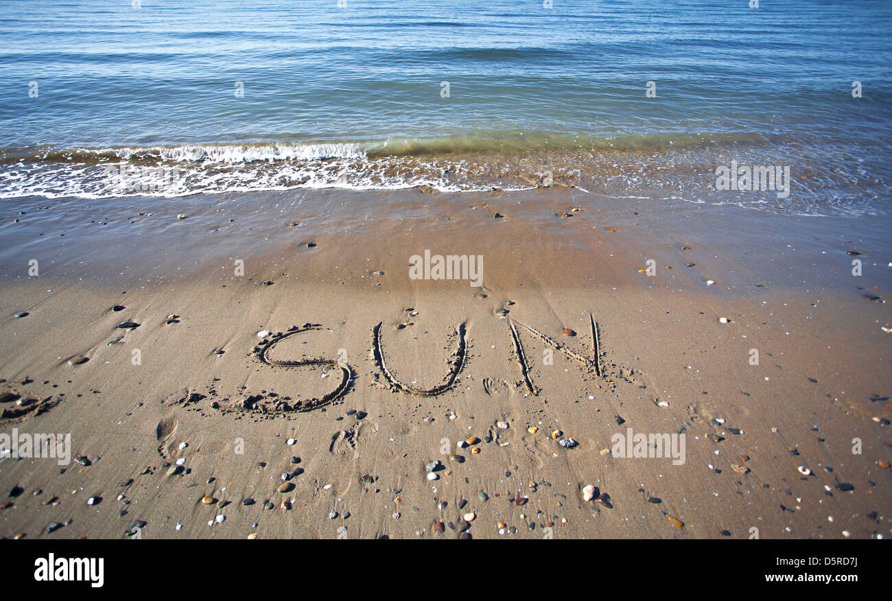 the word sun written in the wet sand  at the beach - Stock Image